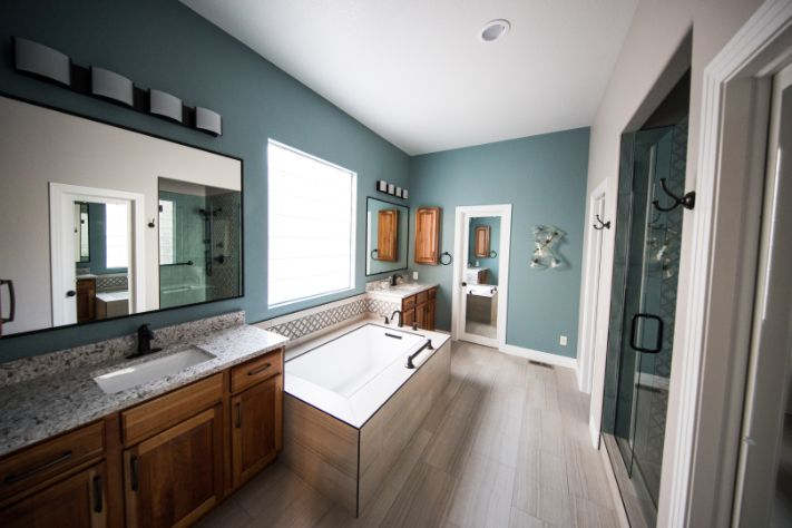 Image shows bathroom painter brooklyn specialist painted bathroom walls with dark blue color. Bathroom turned out to be nice with white vanity and wooden bathroom cabinets. Image was taken in September of 2019