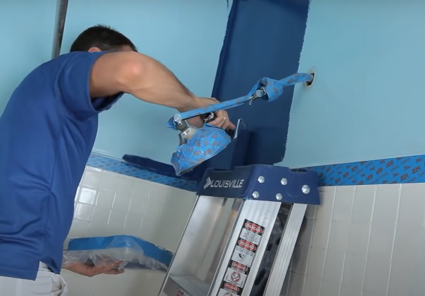 On this image you will see our apartment bathroom painter in NYC painting the wall with washable paint. The choice of color was dark blue. The bath and the sink will be installed later and are of the white color. The combination turned out to be very nice. Image was taken in January 2020