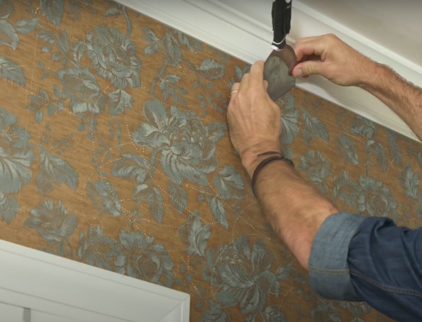 Image shows our apartment wallpaper installation professional gluing wallpaper for our client in his home. Image was taken in 2019 by our wallpaper installer.